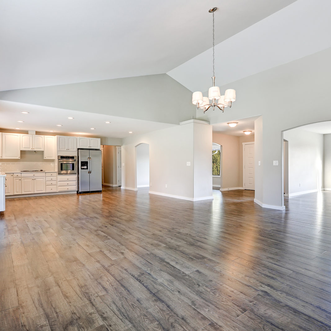 Spacious rambler home interior with vaulted ceiling over glossy laminate floor. Empty light filled dining or living space adjacent to new white kitchen room features pale grey walls. Northwest USA